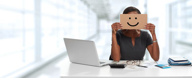 Business woman with smiling cardboard on face Royalty Free Stock Photography
