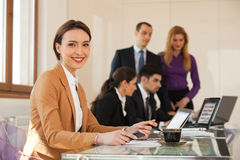 Business woman smiling with colleagues in background Stock Image