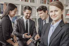Business woman smiling and looking at the camera with her colleagues talking and looking down at a digital tablet in the backgroun Royalty Free Stock Photo