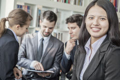 Business woman smiling and looking at the camera with her colleagues talking and looking down at a digital tablet in the backgroun Royalty Free Stock Images