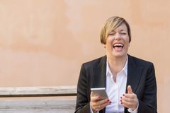 Business woman smiling with a mobile phone on hand. While sitting on a bench Royalty Free Stock Images
