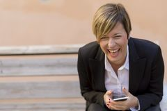 Business woman smiling with a mobile phone on hand. While sitting on a bench Royalty Free Stock Image