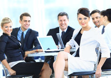 Business woman smiling with people at the back Royalty Free Stock Photography