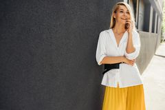 Business woman smiling and standing against gray building`s wall while talking on smart phone. Beautiful student female dressed i. N white shirt, yellow skirt stock photo