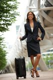 Business woman smiling with suitcase in the city Royalty Free Stock Image
