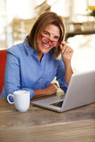 Business woman smiling at table and working with laptop computer Royalty Free Stock Photo