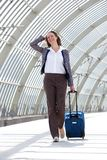 Business woman smiling and walking at station with bag Royalty Free Stock Photography