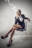 Business woman smoking a cigarette Stock Images