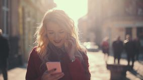 Business woman sms texting using app on smart phone. Attractive girl in red coat walking in the sunshine old city.