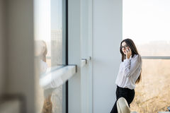 Business woman speak on phone near big office windows Stock Image