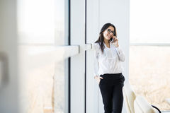 Business woman speak on phone near big office windows Royalty Free Stock Image