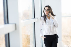Business woman speak on phone near big office windows Royalty Free Stock Photos