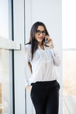Business woman speak on phone near big office windows Stock Photo