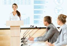 Business woman speaks into a microphone Stock Photos