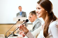 Business woman speaks into a microphone Stock Photo