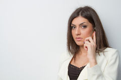 Business woman speaks on mobile serious eye contac Royalty Free Stock Photo