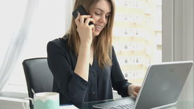 Business woman speaks on the phone in her office, typing on laptop stock footage