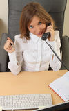 Business woman speeking over the phone. And computer Stock Images