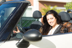 Business woman in sports car. A young successful business woman in a luxurious convertible sports car Stock Images