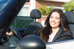Business woman in sports car. A young successful business woman in a luxurious convertible sports car Royalty Free Stock Image
