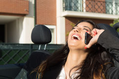Business woman in sports car. A young successful business woman at the phone in her brand new convertible sports car Stock Photography