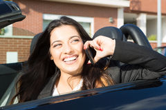 Business woman in sports car. A young successful business woman at the phone in her brand new convertible sports car Stock Images