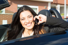 Business woman in sports car. A young successful business woman at the phone in her brand new convertible sports car Stock Photos