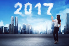 Business woman spraying white 2017 year cloud shape Stock Images