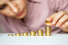 Business woman stacking gold coins into increasing columns Royalty Free Stock Photo