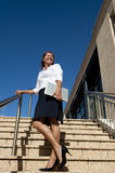 Business Woman on Stairs Outdoor. Upward view of a happy and confident mature businesswoman with a laptop under one arm, wearing a white blouse, black skirt and Royalty Free Stock Photo