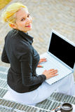 Business woman on stairs working on laptop Royalty Free Stock Images