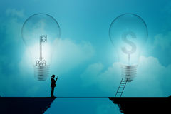 Business woman stand on a cliff with key and dollar signs in light bulbs on a blue background, business concept Royalty Free Stock Photography