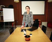 Business woman stand in office with white board presenting. Business woman with notebook stand in office with white board presenting in meeting room Royalty Free Stock Photography