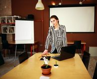 Business woman stand in office with white board presenting. Business woman with notebook stand in office with white board presenting in meeting room Royalty Free Stock Photo
