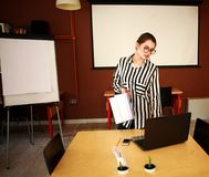 Business woman stand in office with white board presenting. Business woman with notebook stand in office with white board presenting in meeting room Royalty Free Stock Image