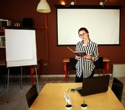 Business woman stand in office with white board presenting. Business woman with notebook stand in office with white board presenting in meeting room Stock Photo