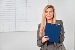 Business woman standing with clipping board in the office and ready to write something. Stock Images