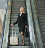 Business woman standing on escalator with travel bags Stock Photos