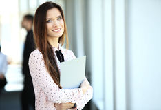 Business woman standing in foreground with a tablet in her hands, her co-workers discussing business matters in Royalty Free Stock Images