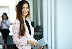 Business woman standing in foreground with a tablet in her hands, her co-workers discussing business matters in Stock Photo