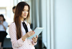 Business woman standing in foreground with a tablet in her hands, her co-workers discussing business matters in Royalty Free Stock Photo