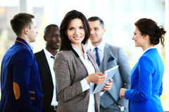 Business woman standing in foreground with a tablet in her hands Stock Image