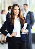 Business woman standing in foreground with a tablet in her hands Royalty Free Stock Image