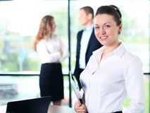 Business woman standing in foreground with a tablet in her hands Stock Photo