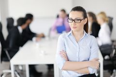 Business woman standing in front of with her staff. Successful business women standing with her staff in background at modern bright office stock image