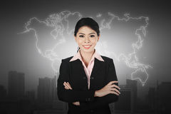 Business woman standing in front of world map. Business globalization concept Royalty Free Stock Photography