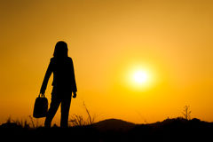 Business woman standing and holding bag at  sunset silhouett. Stock Images