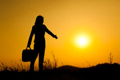 Business woman standing and holding bag at sunset silhouette. Royalty Free Stock Images
