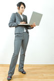 Business woman standing holding laptop. Young business woman standing holding a laptop stock photography