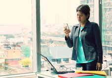 Business woman standing inside office , talking on smartphone and smiling, hearing good news Royalty Free Stock Photo